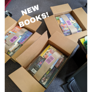 """Image description: Three open cardboard boxes of books with """"New Books"""" overlaid in white text"""