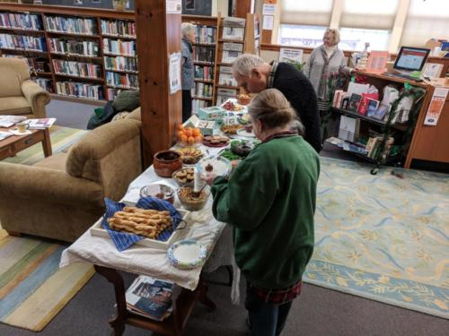 CommuniTEA attendees choosing delicious treats from food table at December 2017 CommuniTEA